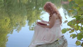 Redhead attractive caucasian girl reading the book in dark red cover on the bank of the lake in the summer forest. Fairy