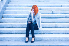 Redhead attractive woman sitting on the stairs reading something with a tablet Stock Images