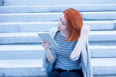 Redhead attractive woman sitting on the stairs, touching her hair and looking at tablet Royalty Free Stock Image