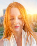 Redhead backlit by the sun closed eyes Stock Images