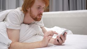 Redhead Beard Man Lying in Bed Scrolling and Browsing on Smartphone stock video