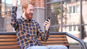 Redhead Beard Young Man Celebrating Win on Smartphone, Sitting Outdoor on Bench. 4k high quality, 4k high quality stock footage