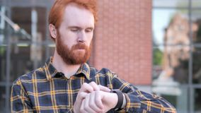 Redhead Beard Young Man Using Smartwatch Outdoor. 4k high quality, 4k high quality stock footage