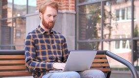 Redhead Beard Young Man working on Laptop, Sitting Outdoor on Bench. 4k high quality, 4k high quality stock video