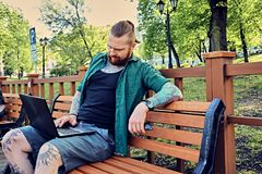 Redhead bearded hipster male using laptop in a park. Redhead bearded hipster male in a green fleece shirt using laptop in a park Royalty Free Stock Photography