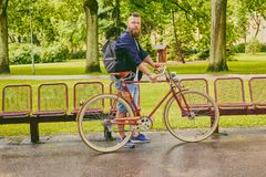 Redhead bearded male on a retro bicycle in a park. Redhead bearded hipster male on a retro bicycle in a summer park royalty free stock photo