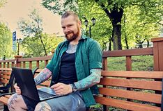 Redhead bearded hipster male using laptop in a park. Redhead bearded hipster male in a green fleece shirt using laptop in a park Stock Images