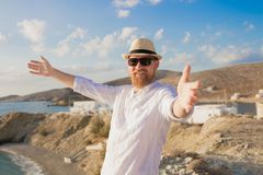 Redhead bearded hipster traveler man with open hands in hat and sunglasses smiling against the blue sea and sky background stock photos