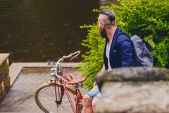 A man on a retro bicycle in a park. Redhead bearded male dressed in a blue jacket and jeans on a retro bicycle in a park stock photo