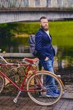 A man on a retro bicycle in a park. Redhead bearded male dressed in a blue jacket and jeans on a retro bicycle in a park royalty free stock photo
