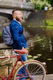 A man on a retro bicycle in a park. Redhead bearded male dressed in a blue jacket and jeans on a retro bicycle in a park stock image