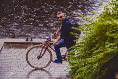 A man on a retro bicycle in a park. Redhead bearded male dressed in a blue jacket and jeans on a retro bicycle in a park royalty free stock image