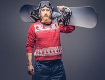 Redhead bearded male in a winter hat with protective glasses dressed in a red sweater, posing with a snowboard on his royalty free stock image