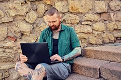 Bearded male using laptop. Redhead bearded tattooed male dressed in a green fleece shirt sits on a steps and using laptop over stone wall Stock Photos