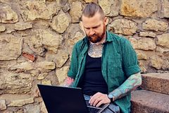 Bearded male using laptop. Redhead bearded tattooed male dressed in a green fleece shirt sits on a steps and using laptop over stone wall Royalty Free Stock Photography