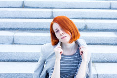 Redhead beautiful businesswoman with a jacket sitting on the stairs with a thoughtful look Stock Photo