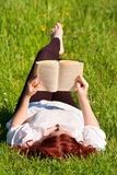 Redhead beautiful girl reading a book in nature. Lying on the grass Royalty Free Stock Image