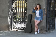 Redhead beautiful girl in the street with a guitar in the case royalty free stock photo