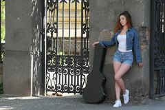 Redhead beautiful girl in the street with a guitar in the case stock photos