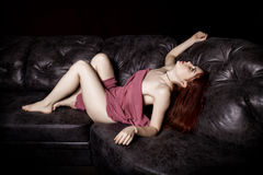 Redhead beautiful sexy young woman lying on a black leather sofa on a black background Stock Photography