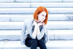 Redhead beautiful woman with a jacket sitting on the stairs with a thoughtful look Stock Photos