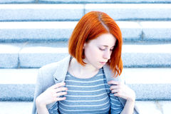 Redhead beautiful woman with a jacket sitting on  stairs with a thoughtful look Royalty Free Stock Image