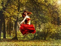 Redhead beautiful woman in red dress dancing in a autumn forest. Stock Photos