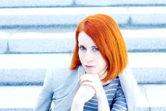 Redhead beautiful young businesswoman with a jacket sitting the stairs. Redhead beautiful young businesswoman with a jacket sitting on the stairs with a Royalty Free Stock Photography