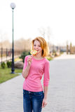 Redhead beautiful young woman biting a lollipop. Pretty girl having fun outdoors. Royalty Free Stock Images