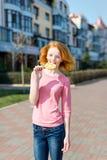 Redhead beautiful young woman biting a lollipop. Pretty girl having fun outdoors. Stock Images