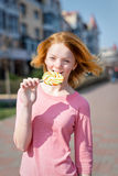 Redhead beautiful young woman biting a lollipop. Pretty girl having fun outdoors. Royalty Free Stock Photo