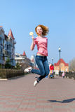 Redhead beautiful young woman jumping high in air over blue sky holding colorful lollipop. Pretty girl having fun outdoors. Stock Photo