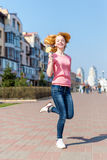 Redhead beautiful young woman jumping high in air over blue sky holding colorful lollipop. Pretty girl having fun outdoors. Royalty Free Stock Photos