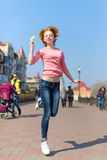 Redhead beautiful young woman jumping high in air over blue sky holding colorful lollipop. Pretty girl having fun outdoors. Royalty Free Stock Images