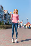 Redhead beautiful young woman jumping high in air over blue sky holding colorful lollipop. Pretty girl having fun outdoors. Stock Image