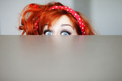 Redhead beauty. Funny girl hiding behind a table Royalty Free Stock Photo