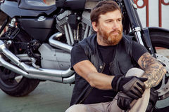 Redhead biker with beard in leather jacket and his bike. royalty free stock images
