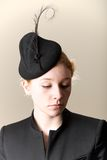 Redhead in black feathered hat looking down Royalty Free Stock Photos