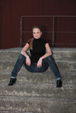 Redhead blue jeans. Pretty cute red long haired teen girl with black top and blue jeans is sitting with spreaded legs on concrete stairs Royalty Free Stock Photography