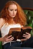 Redhead bonito que lê uma Bíblia Fotografia de Stock Royalty Free