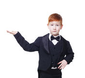 Redhead boy in tailcoat tuxedo point somewhere, isolated on white Royalty Free Stock Photography
