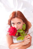 Redhead bride. Young attractive woman in bridal dress, with red rose held close to her face Royalty Free Stock Image