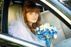 Redhead bride sitting in car and holding blue wedding bouquet Stock Photography