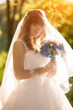 Redhead bride standing in beam of light and holding bouquet unde Stock Images