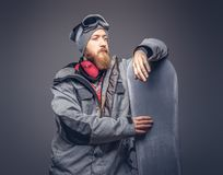 Brutal redhead snowboarder with a full beard in a winter hat and protective glasses dressed in a snowboarding coat royalty free stock photo