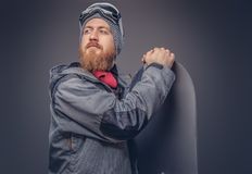 Brutal redhead snowboarder with a full beard in a winter hat and protective glasses dressed in a snowboarding coat royalty free stock photos