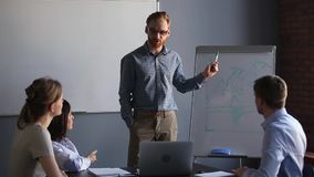 Redhead business coach giving presentation to company staff use flipchart. In boardroom gather red-haired business coach giving presentation to company staff stock footage