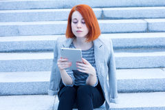 Redhead business woman sitting on the stairs reading something with a tablet Stock Photography