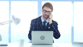 Redhead Businessman Talking on Phone, Attending Call at Work. 4k , high quality Royalty Free Stock Images