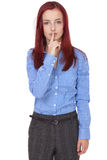 Redhead businesswoman holds finger on her lips Royalty Free Stock Photo
